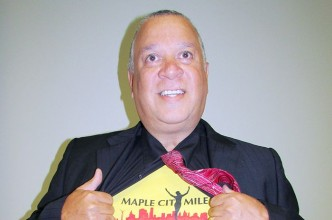 """""""Superman"""" Doug Robbins proudly rips open his dress shirt to display the Maple City Mile T-shirt underneath."""