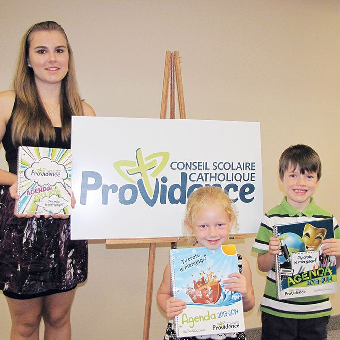Pain Court students Marie-Josée Vercouteren, Leah Cromwell and Cameron Schinkelshoek hold new school agendas with the French catholic school board's new name and logo. The new name – Conseil scolaire catholique Providence – was unveiled Monday. School board officials said the new name modernizes and simplifies the board's identity.