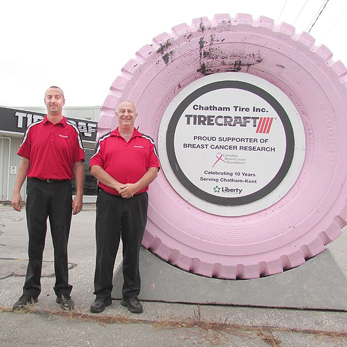 Tim and Mark Legacy, of Chatham Tirecraft, stand proudly beside their pink tire, which they have displayed for the past two years thanks to their donations to battle breast cancer.