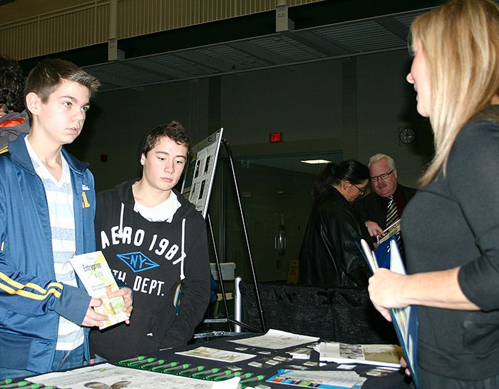 Ryan Swackhammer, left, and Greg Bolohan, Grade 10 students at École secondaire de Pain Court, listen to Rosemary Montgomery, small business consultant for the Chatham-Kent Small Business Centre, at the second annual Career Fair held at the Thames Campus Thursday.