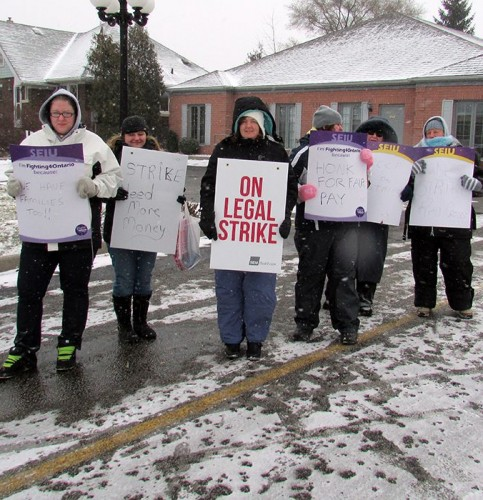 A group of personal support workers picket outside the Red Cross office on Grand Avenue in Chatham Wednesday morning.