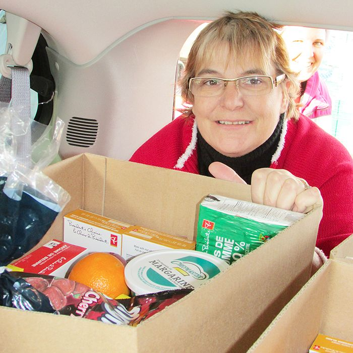 Mary Ann Wieringa packs a van with food Thursday at St. Joseph's Auditorium as part of the food delivery for Chatham Goodfellows. Vans and trucks lined up beside the auditorium as volunteers jammed them full of food, destined to land on tables of families in need in Chatham this holiday season.