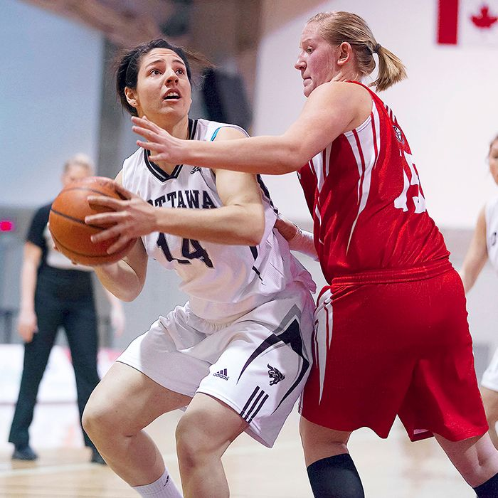 Shauney Fischer guards an Ottawa Gee Gee in Ontario women's university basketball. Fischer and Erin Sarapnickas are Wallaceburg athletes who've bonded even closer since going away to school. (Photo by Richard A. Whittaker)