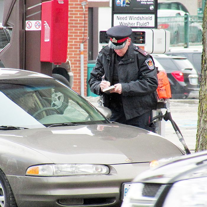 Const. Mike Currie writes out a ticket during today's safety blitz at the corner of Grand Avenue and St. Clair Street in Chatham.