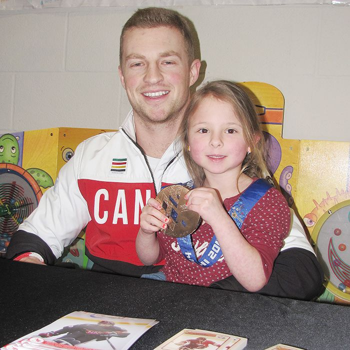 Brianna McLellan, 5, tries on Derek Whitson's bronze medal at the Children's Treatment Centre in Chatham. Whitson and the Canadian men's sledge hockey team won the medal at the 2014 Paralympics in Sochi, Russia. The centre hosted a celebration for Whitson on March 20.