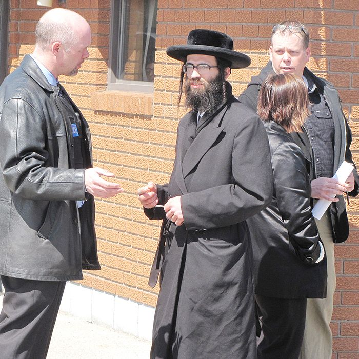 A man from the Lev Tahor community speaks with members of the Chatham-Kent Police Service and the Children's Aid Society following a raid by the Canada Border Services Agency Wednesday that resulted in several arrests.