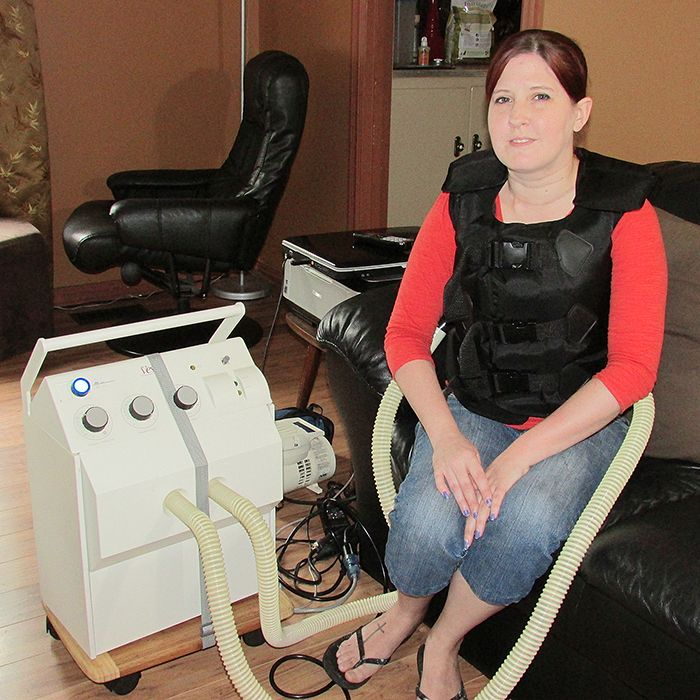 Julie Rice demonstrates how she spends an hour a day connected to a vest and a machine that vibrates her torso to help loosen thick mucus that forms in her lungs as a result of cystic fibrosis.