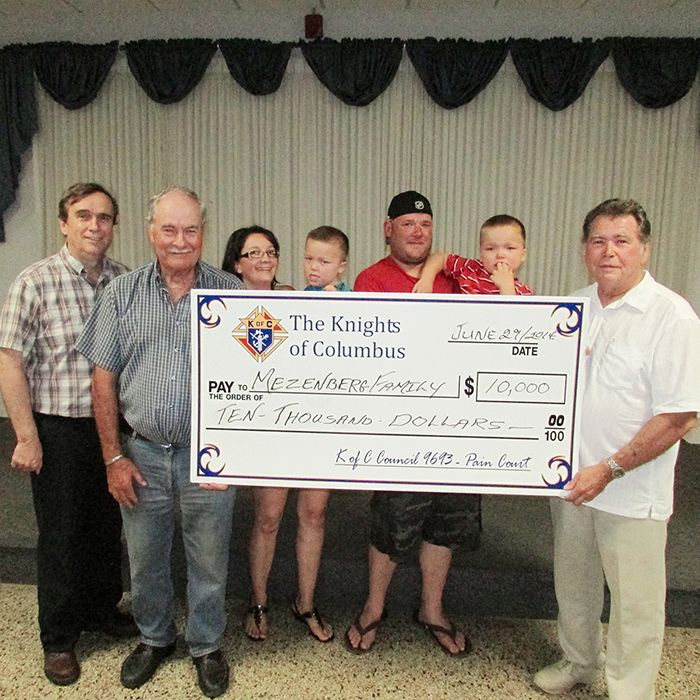 From the Mezenberg family, Krista, holding Max; and Justin, holding Alex, accept a cheque for $10,000 from Wild Game Supper organizers Yvon Sterling, grand knight of Knights of Columbus council 9693, left; Bob Branquet, dinner organizer; and Norb King, right, chairman of the Wild Game Supper committee with the Knights of Columbus. The Mezenbergs will use the money to make modifications for their home and vehicle, as the two boys are developmentally delayed.