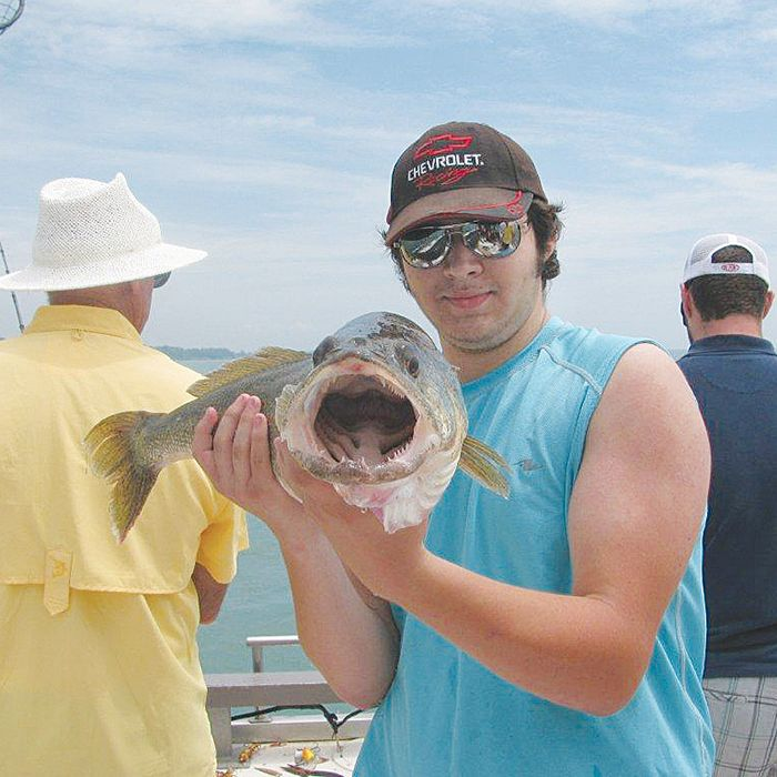 A satisfied customer of Butcher Buoy Charters holds a massive walleye.