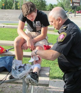 Declan Cook of Tilbury gets some fake blood poured into his equally fake leg wound at a mock accident July 10 at Percy Park in Chatham by Assistant Fire Chief Ric Scharf. Cook took part in a week-long summer camp that exposes local high school students to various health-care and emergency services professions. The 10 local kids played victims at the mock accident, where a car was to have run into the bleachers at a ball field, as well as members of the emergency services called in to aid the injured.