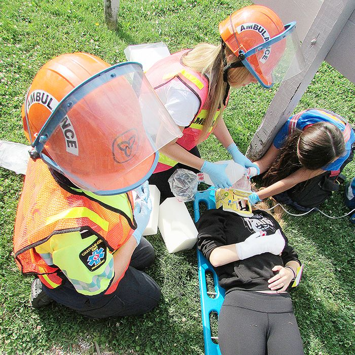 A paramedic and students working alongside emergency personnel tend to Sarina LeBlanc, a mock accident victim of was to have suffered a compound fracture of her forearm and was knocked unconscious. The scenario involved a car running into the bleachers at a ball field.