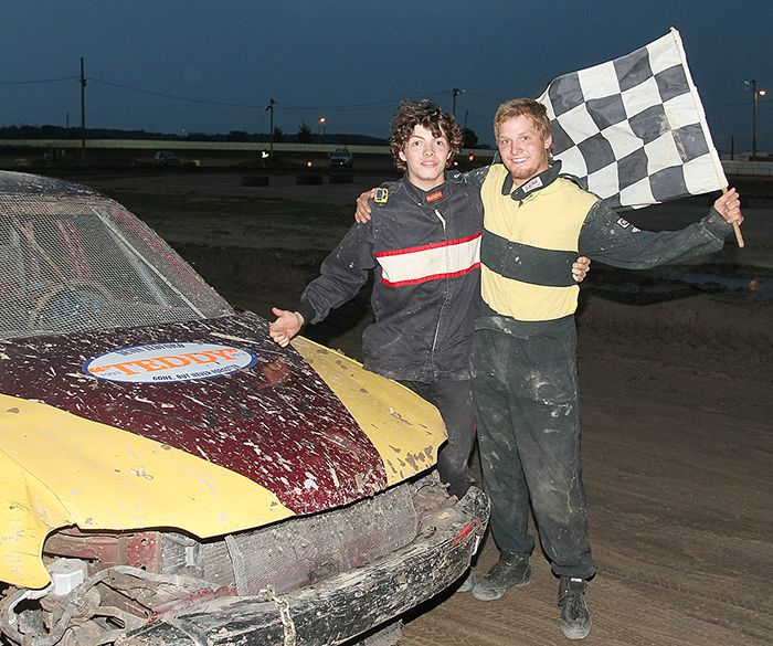 Blenheim drivers Shawn Hope, right, waves the checkered flag, with Jeff Schives, left, who presented a trophy in memory of his brother Cory to Hope after winning the July 26 feature. Schives has six feature wins and Hope five, as both drivers have 14 checkereds heading into Saturday's AutoTech Bombers season championship race.