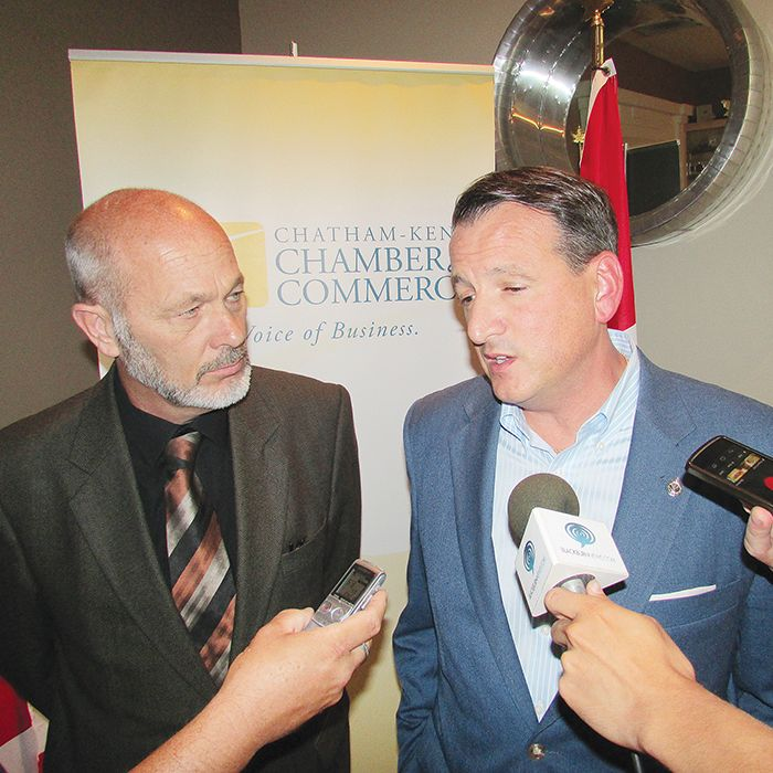 Local MP Dave Van Kesteren, left, looks on as Greg Rickford, federal minister for natural resources, and the federal economic development initiative for Northern Ontario, speaks to the media in Chatham Friday.