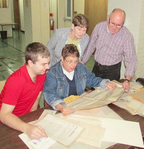Devon Hansen, Edwina Rawlings, Brenda Kent and John Keech examine some letters from the late 19th century regarding St. Andrews United Church.