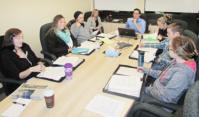 Dean Hale, Chatham-Kent's youth entrepreneurship consultant, seated at the head of the table, and Rosemarie Montgomery, small business consultant, left, work with a group of young entrepreneurs.