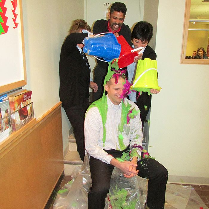 LCBO auditor Jeff Dunlop gets slimed and feathered by Wellington Street LCBO staff Friday. From left, Anita VanDongen, Darren Lopes, and Maria Mariconda were quite happy to take part in the United Way fundraiser.