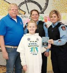 Back row, from left Chatham Optimist member Stevan Tuinstra and CKPS Spec. Consts. Brenda Koldyk and Randi Hull present Marly Pollock, front, with her award for providing the winning design in the VIP T-shirt contest.