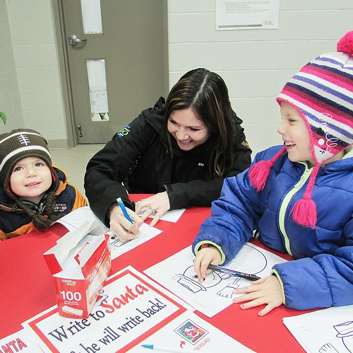 """Avery Stewart, 7, right, reacts after her brother, Chase, 3, told The Chatham Voice what he wants for Christmas: """"Presents!"""" Mom Cheryl can only smile at the interaction as the family fills out letters to Santa at Christmas in the Village, which took place at the Chatham-Kent Children's Safety Village Dec. 11. Chase later admitted those presents could include such items as cars and space games."""