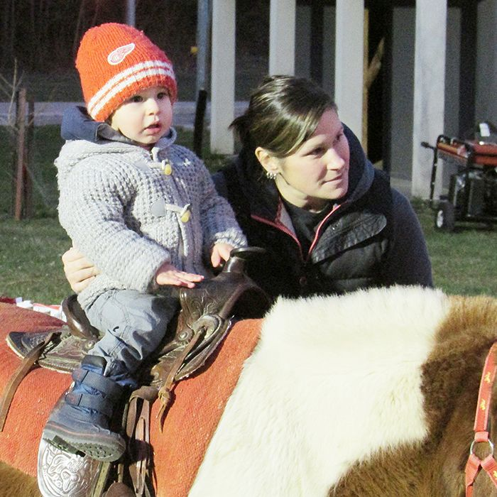 Lincoln Pfaff, 2, waits his turn for a ride on the TJ Stables ponies at Christmas in the Village Dec. 11, while his mom, Jackie, offers support.