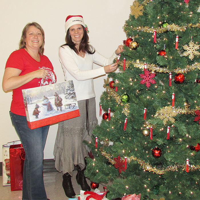 "For more than a decade, volunteers, local businesses and staff at Chatham-Kent Children's Services have come together to make the holiday season just a little bit brighter for ""their kids,"" former crown wards ages 18-21 who have now exited the system. Here, Tammy Craeymaersch and Angela Makra of the Chatham-Kent Children's Services (CKCS) finish trimming the tree."
