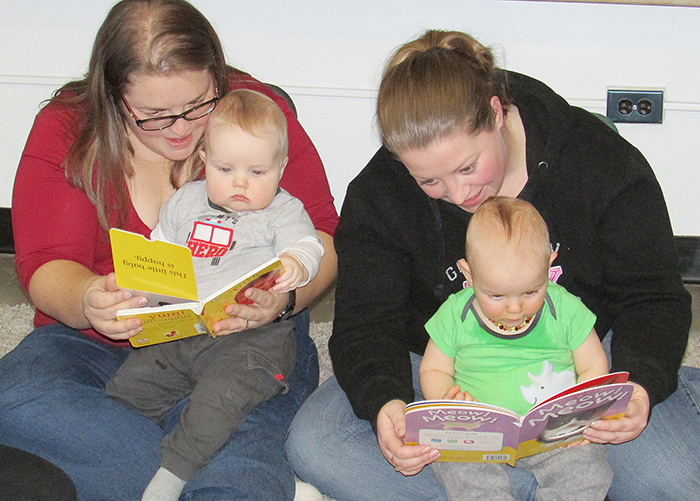Jenni Matthys, left, and Carter, along with Megan Tricker and Landen Deschene enjoy time sharing books as part of the Ontario Early Years Centre Reading Party Tuesday afternoon at Queen Elizabeth School. The event was part of Family Literacy Day.