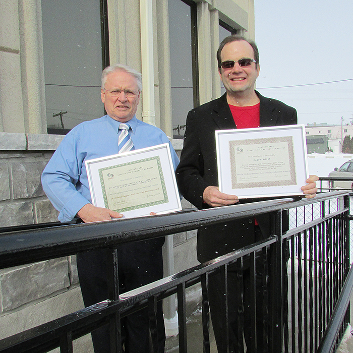 Murray McLauchlin and Ralph Roels showcase awards they received Tuesday from the Chatham-Kent Accessibility Advisory Committee. The McLauchlin Wellness Clinic in Blenheim was named this year's most accessible business, while Roels, head of the committee, earned an advocacy award.