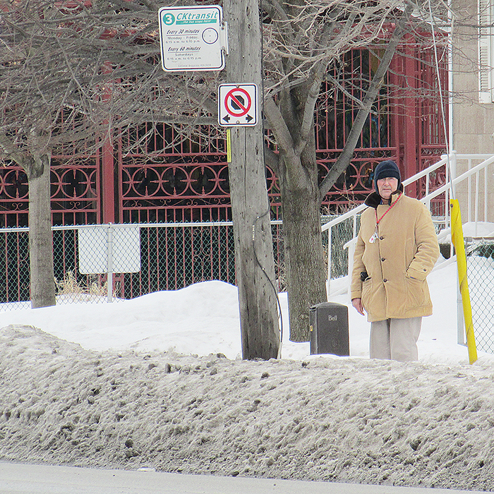 A man waits for a CK Transit bus on Park Avenue East recently, facing a snow bank as tall as his knees that he'll have to navigate when the bus arrives.