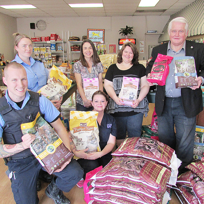 John Cryderman, right, and Joanne Bondy of Cats & Dogs Smart Pet Food, top middle, donated more than $2,000 worth of pet food and kitty litter to the OSPCA Friday. OSPCA staffers Ryan Sparks, Nicole Cassel, Amber Ogle, and Robyn Brady loaded the goods into two trucks for transport back to the shelter. Someone robbed the OSPCA recently of $500 worth of dog food.