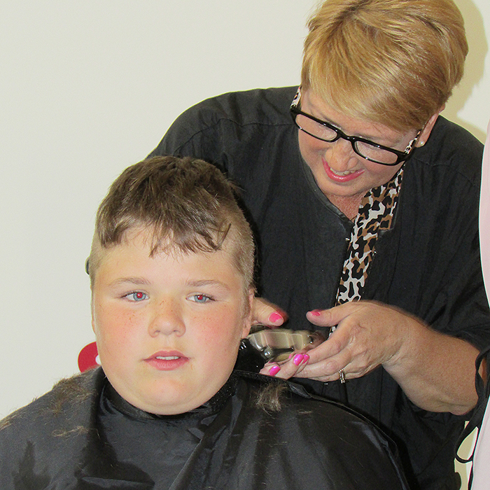 Dean Bonner, 10, son of Chatham-Kent Police Service Const. Amy Finn gets his hair sheared off as part of the annual Cops for Cancer fundraising event Friday.