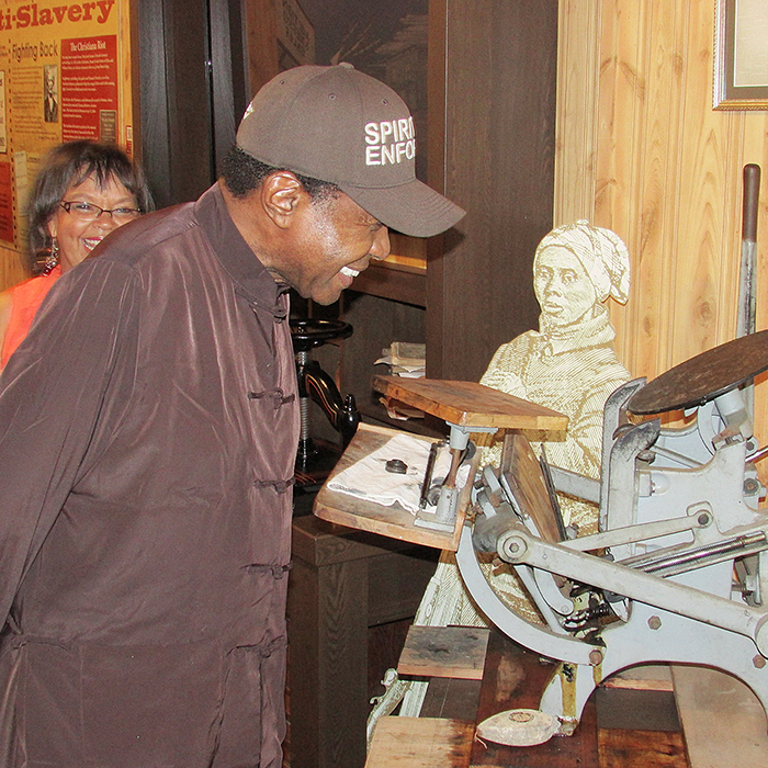 Ben Vereen examines the printing press of Mary Ann Shadd Cary, the first black woman newspaper publisher in North Ameria and the first female publisher in Canada. Vereen toured the Buxton Museum and National Historical site while on a break from his performances at Victoria Playhouse in Petrolia. Looking on is museum curator Shannon Prince.