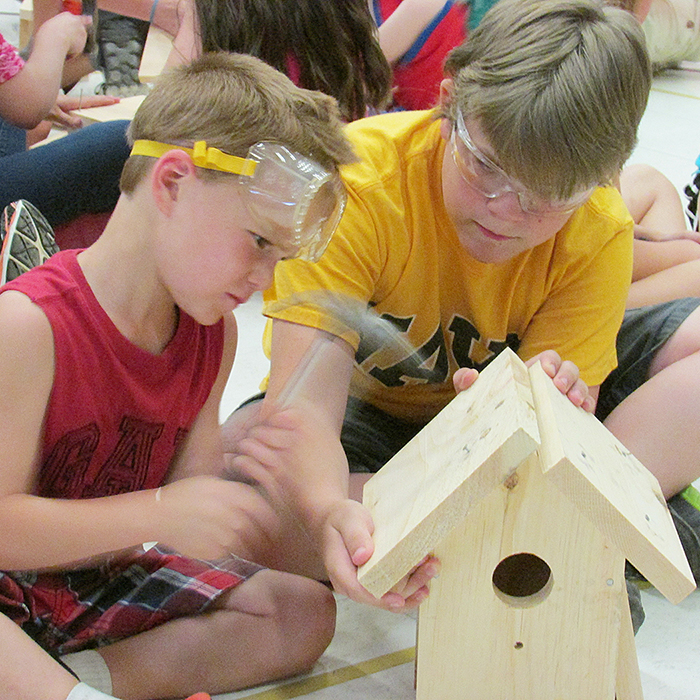 St. Vincent senior kindergarten student Camden Arnold gets some help from Grade 6 student Evan Girard in building a birdhouse. Students at the school spent some time recently building the houses in memory of Ron Stevens, the husband of principal Nicole Stevens.