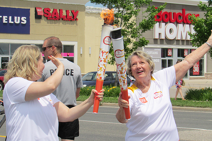 Chatham resident and torch bearer Kendra Shurgold completes her 200 metres and passes the flame to Diane Easton, 77, of Chatham during the 2015 Pan Am Games Torch Relay as it made its into north Chatham Tuesday afternoon from Wallaceburg.