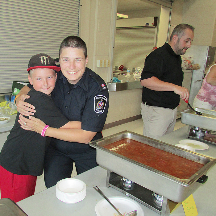 Const. Amy Finn, right, gets a big hug from Joey Reid, 11, at the annual community luncheon Friday. Members of the local police association, as well as East Side Pride put on the event.