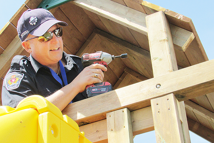 Const. Paul Myers of the Chatham-Kent Police Service puts the finishing touches on Michael's play set.