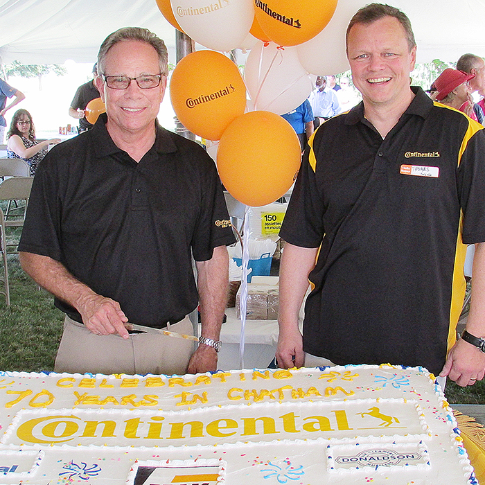 Classic cars, cake and public tours were all part of the 70th Anniversary celebration of Continental Tires in Chatham on Saturday at the Park Street East facility. Employees, the public and local dignitaries were on hand to join in the celebration as Bill Gillier, director of actuators, left, and Thomas Stierle, vice-president of actuators from Germany cut the cake before beginning tours of the facility. (Mary Beth Corcoran photo)