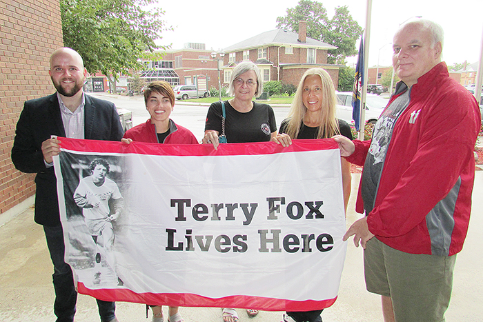 Chatham-Kent Council member Brock McGregor, left, stood with members of the Chatham Terry Fox Run committee during a flag-raising ceremony at the Civic Centre in Chatham Friday. From left is event organizer Jessica Barton with committee members Mary Helen Blue and Lori Timpson and participant Pat McMahon.