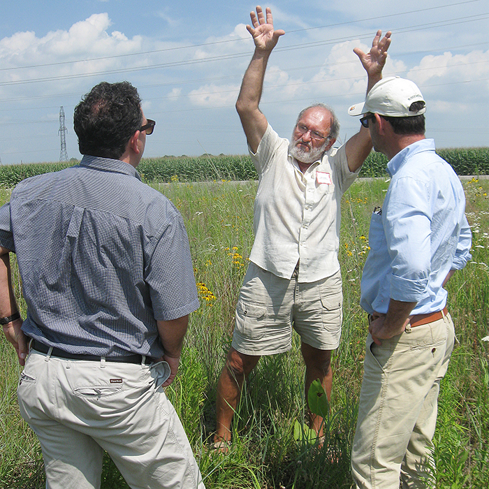 """International CiB judges, Richard Daigneault (left) and Alain Cappelle (right) are captivated by Sydenham Field Naturalist Larry Cornelis as he describes some of the tall grass prairie species that have been reintroduced at Peers Wetland outside Wallaceburg. It was a perfect example of one of CK's many pollinator-friendly initiatives and most certainly contributed to being named Canada's """"Most Pollinator-Friendly Community"""" at the National CiB Ceremonies held in Kamloops, BC on Oct. 3."""