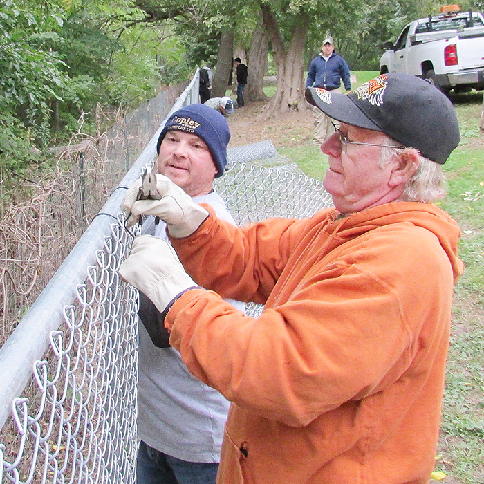 Gordon Wathy, left, holds a length of chain link fence in place while Ron Rush ties it in place Saturday morning at the off-leash dog park on Water Street in Chatham.