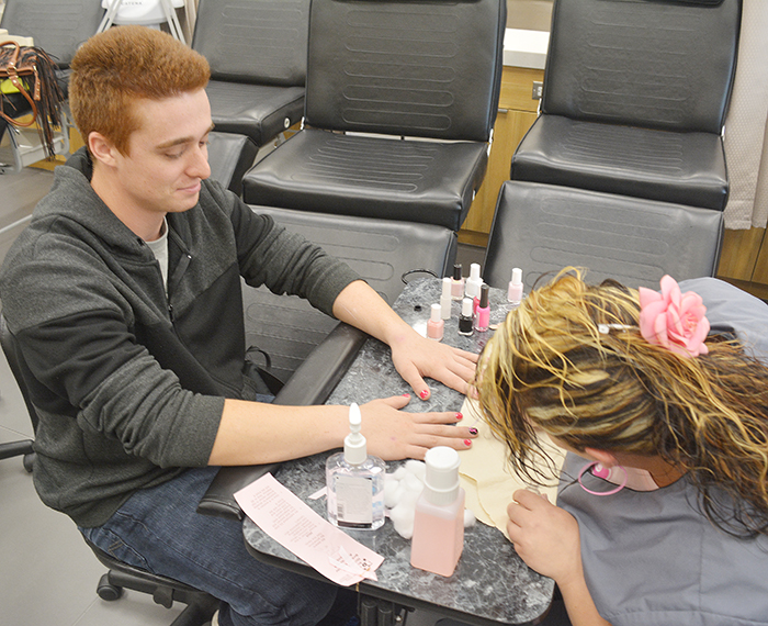 The Esthetician program at St. Clair College raised a total of $1,000 by painting nails Friday. Here student Jen Stekelenburg applies the finishing touches to Devin Manning, a power line technician student.