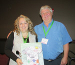 Dr. Leena Augimeri receives a painting from Mike Neuts, whose Make Children Better Now organization sponsored the recent children's mental health summit in Chatham.