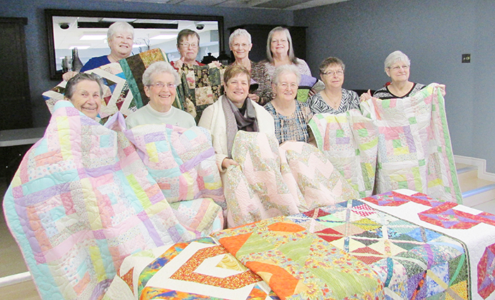 Members of the Stitchin' Sisters donate 10 quilts to the Chatham-Kent Hospice. Front row, from left, Stella Gleason, Jane Jenner, Michelle O'Rourke (director of Hospice services), Marlene Warren, Mary Deturck and Barb Slavik. Back row, Barb Chandler, Diane Tatchell, Marlene Ternoey and Joanne Smith. There are 10 suites at the hospice, and now each will have its own unique quilt.