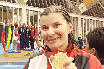 Patricia Wright proudly holds the gold medal she won at the Karate Canada championships in British Columbia, The 39-year-old trains at the Zanshin Dojo Karate Club in Chatham.