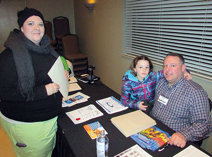 Kellie Barnes registers her team for the 2016 Relay for Life fundraiser held by the Canadian Cancer Society. Taking her registration is volunteer committee member Jamie Rioux while his eight-year-old daughter Kelsey looks on.