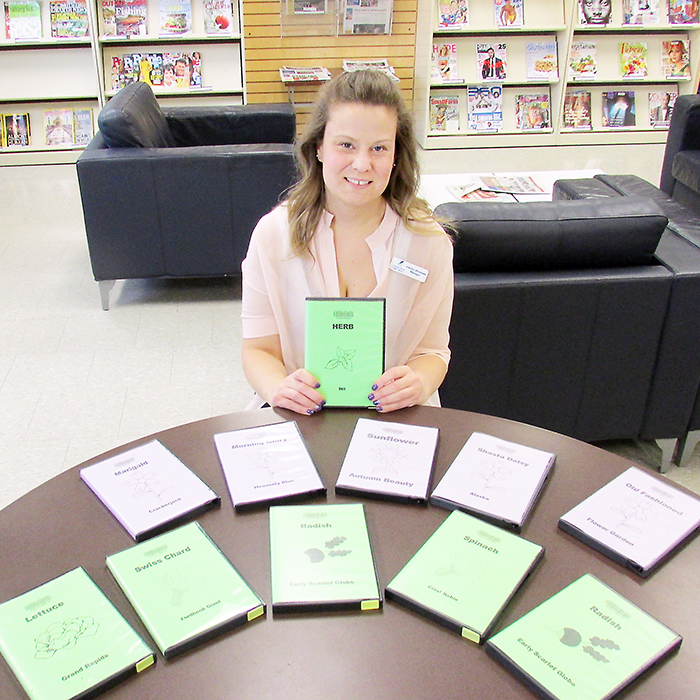 """Chelsie Abraham, manager of public services at the Chatham-Kent Public Library, shows off packets of seeds available for lending. More than 50 varieties of fruits, vegetables, herbs and fruits are available to be """"loaned."""""""
