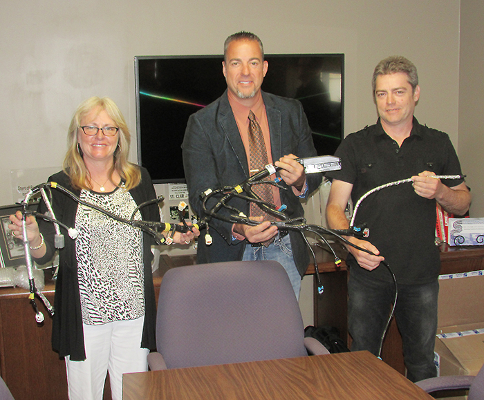Jody Pilon, Charlie Hess and Randy Hess hold one of the automotive wiring harnesses designed by St. Clair Technologies of Wallaceburg. The firm recently celebrated 65 years in business.