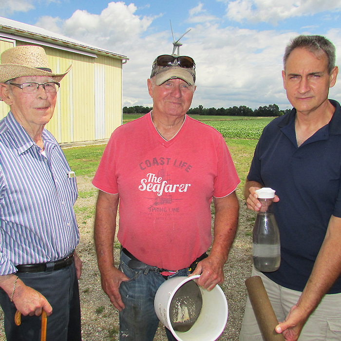 Marsh Line farmer Laurier Cartier and former MP Rex Crawford, left, stand with activist and Water Wells First organizer Kevin Jakubec, showing the clogged water filter and silt/water mixture that is tainting his well water since the wind turbine project on Marsh Line was put in more than years ago.