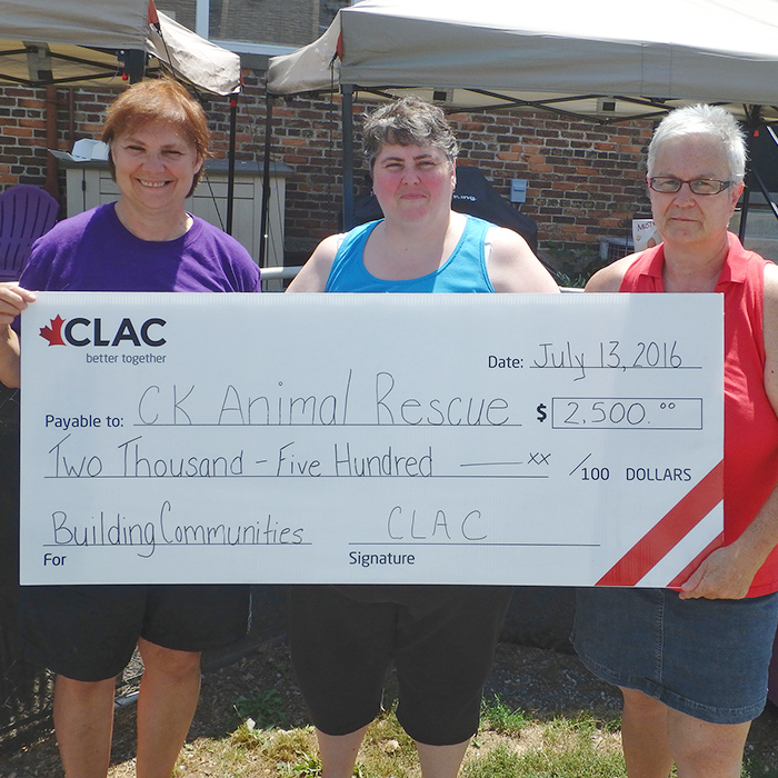 C-K Animal Rescue personnel Nancy Ball and Susan Nixon accept a donation of $2,500 from CLAC member Laurie King.
