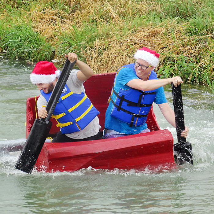 Santa's helpers, alias Ryan Feddes, left, and Nick Cadotte, put his sleigh to a new challenge Saturday in the cardboard boat race at WAMBO. The event attracted 12 entries and was viewed by hundreds of people cheering from shore. The Homeward Realty team won the event.