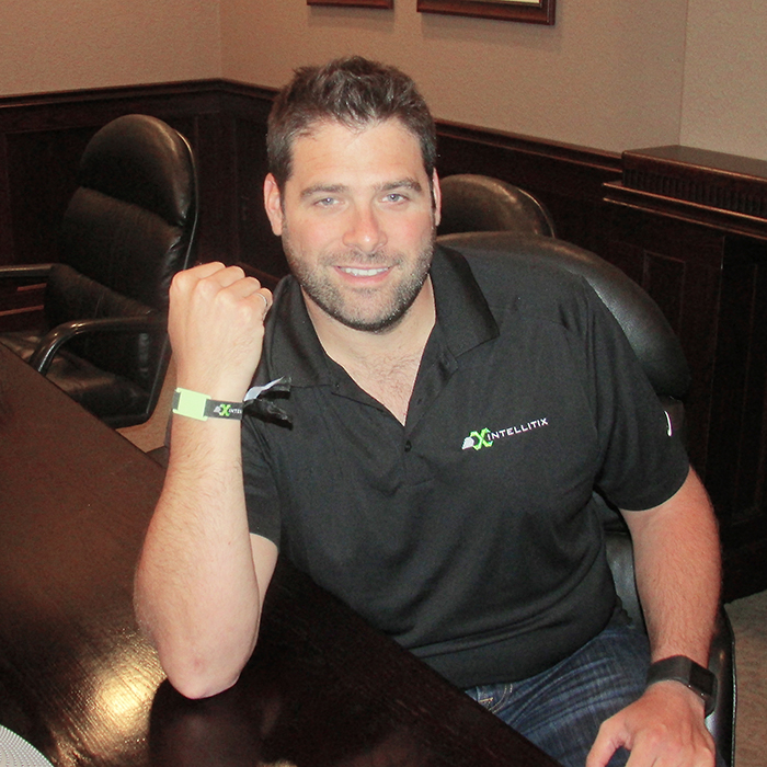"""Intellitix Chief Operating Officer Peter Fantuz shows one of the RIFD wristbands used by his firm create a """"cashless experience"""" for events from concerts to food festivals."""