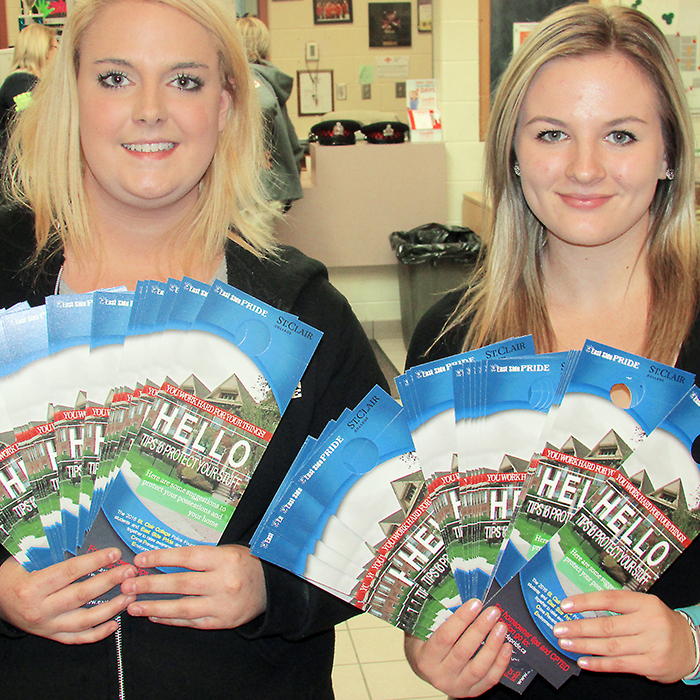 Kayla Hodgson (left) and Taylor Lorlarue show some of the 2,000 door knockers being distributed throughout the community by East Side Pride and students from the St. Clair College Police Foundations program.